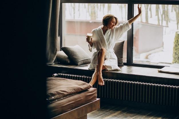 自宅の窓辺でバスローブでコーヒーを飲む女性