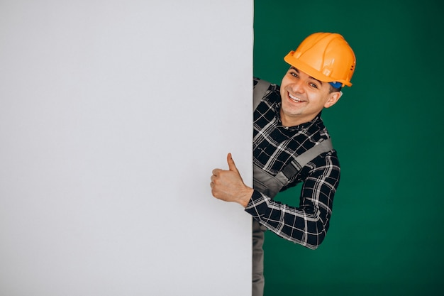 緑の壁に分離されたハード帽子の男性労働者