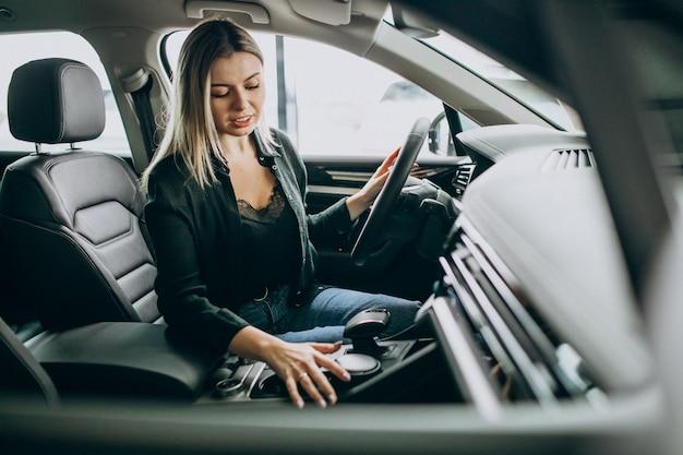 Молодая женщина, тестирование автомобиля в автосалоне