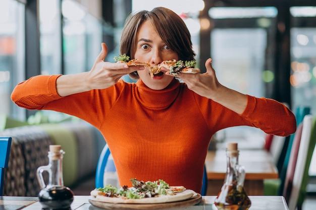 ピザバーでピザを食べる若いきれいな女性