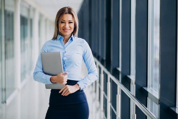 オフィスで立っているラップトップを持つ若いビジネス女性