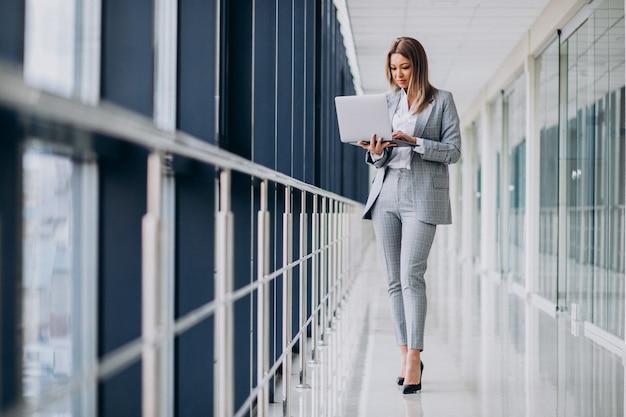 Молодая бизнес-леди работая на компьтер-книжке в компьютере