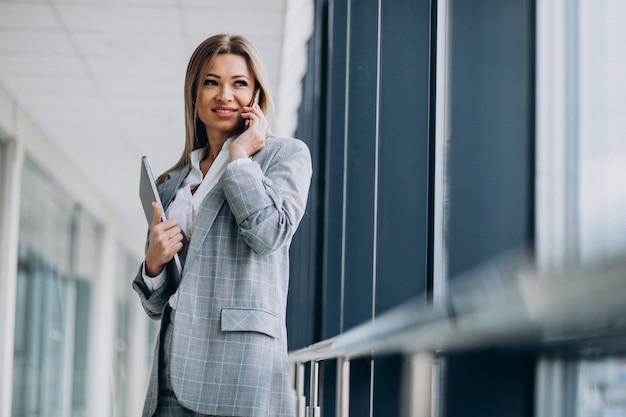 Привлекательная деловая женщина разговаривает по телефону в офисе