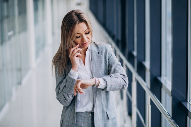 ターミナルで電話で話している若いビジネス女性