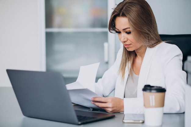 オフィス内のコンピューターで作業し、コーヒーを飲む美しいビジネス女性