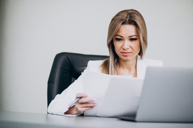 オフィスのコンピューターで作業して魅力的なビジネス女性