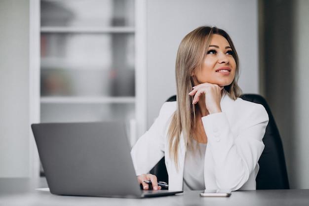 オフィスでラップトップに取り組んでいる若いビジネス女性