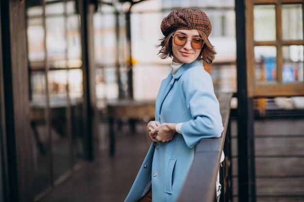 Модель молодой женщины в синем пальто у кафе
