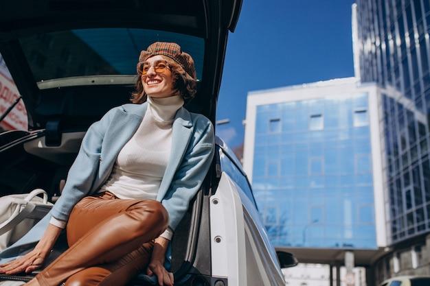 Молодая женщина сидит в задней части автомобиля, разговаривает по телефону