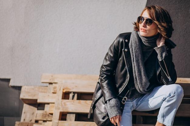 Модель молодой женщины в кожаной куртке вне улицы