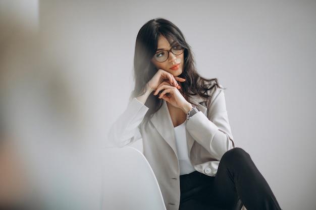 Портрет молодой женщины, сидя в офисе
