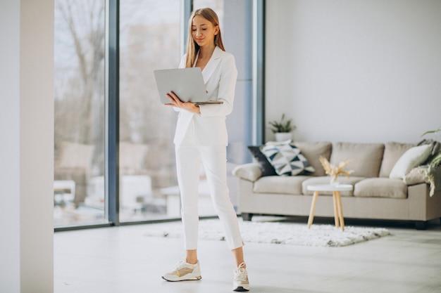 コンピューターに取り組んでいる白いスーツの若いビジネス女性