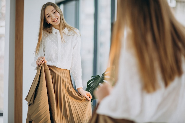 Милая молодая женщина в вскользь обмундировании смотря в зеркало