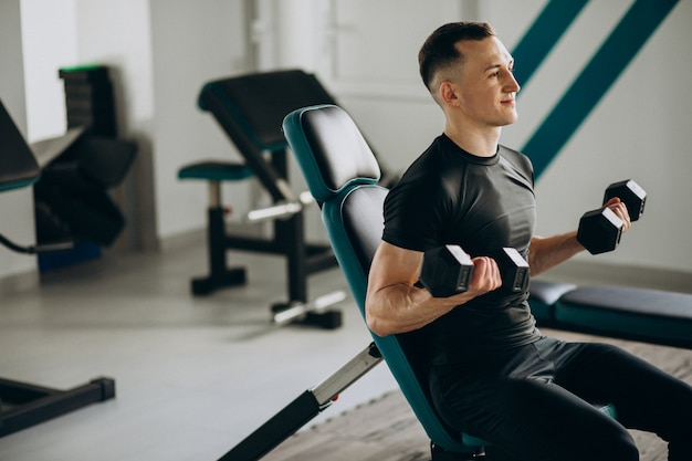 Молодой спортивный человек тренируется в тренажерном зале
