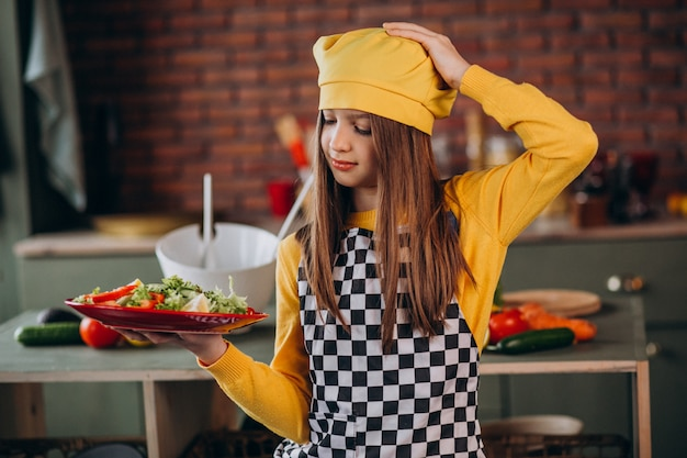 キッチンで朝食のサラダを準備する若い十代の少女