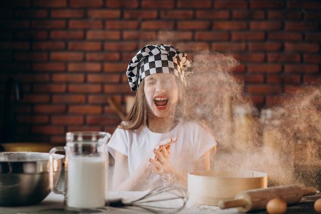 朝食のキッチンでペストリーを焼く少女