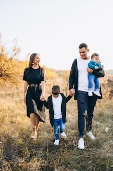 公園を歩いて幼い息子を持つ若い家族