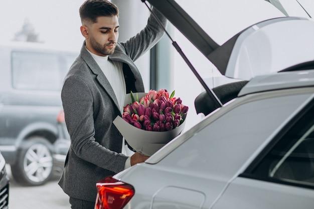 美しい花の花束を提供する若いハンサムなビジネス男
