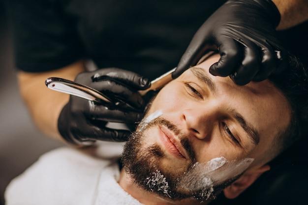 Красивый мужчина стричь бороду в парикмахерской