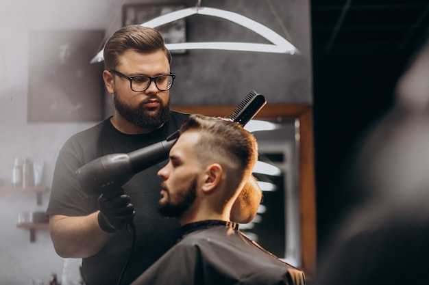 理髪店の髪をスタイリングでハンサムな男