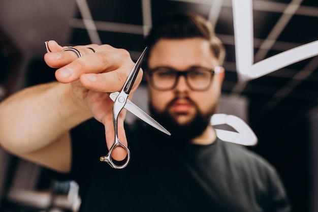 理髪ツールを持つプロのヘアスタイリストをクローズアップ