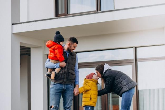 Молодая семья с двумя маленькими братьями у дома