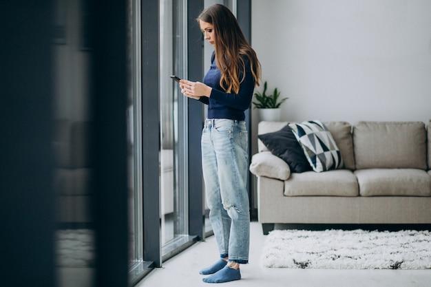 若い女性が窓際で電話のキーボードを入力