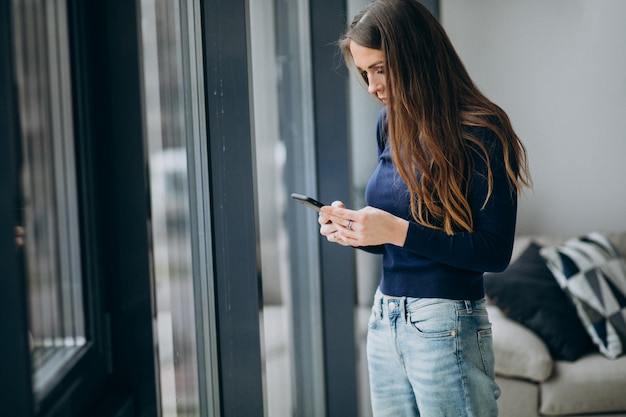 Молодая женщина печатает на клавиатуре телефона у окна
