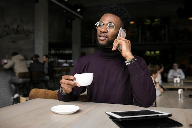 Используя планшет американского афро-американского бизнесмена