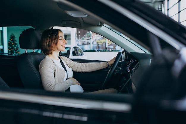Молодая беременная женщина, тестирование автомобиля в автосалоне