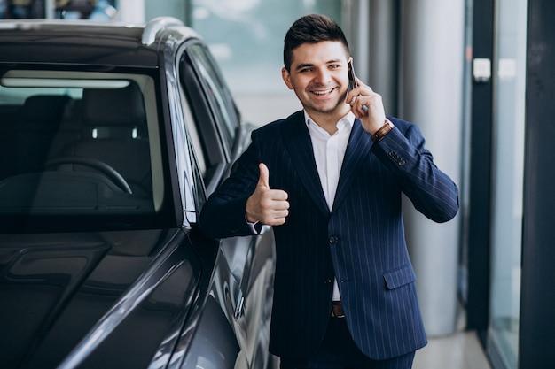 Молодой красивый деловой человек в автосалоне, выбирая автомобиль