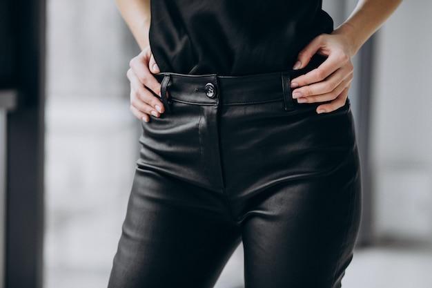 Модель молодой женщины в черных кожаных брюках