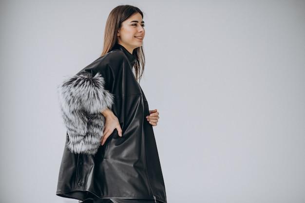 Модель молодой женщины в длинном черном кожаном плаще