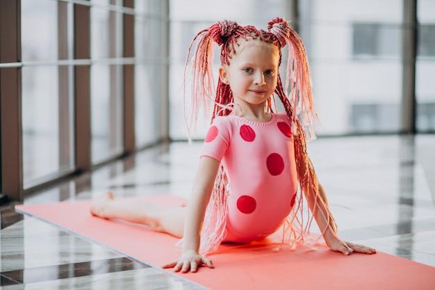 Милая маленькая девочка, делая гимнастику на коврике