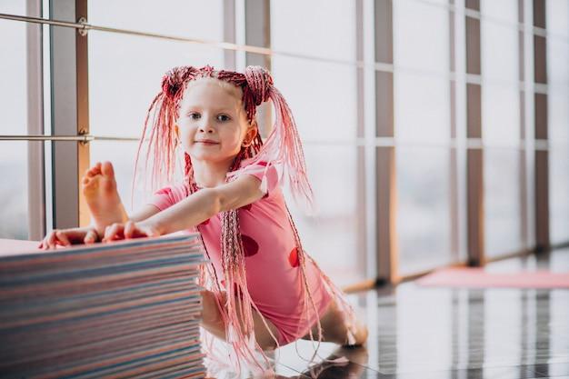 Милая маленькая девочка, делая гимнастику на коврик в студии