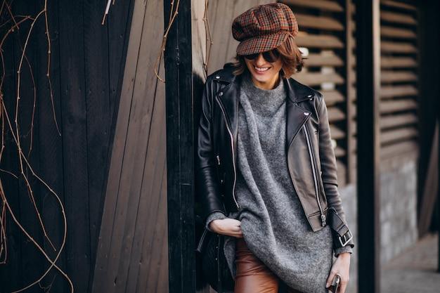 Молодая красивая женщина в кожаной куртке вне улицы