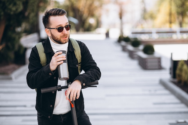 スクーターに乗って、魔法瓶からコーヒーを飲むハンサムな男