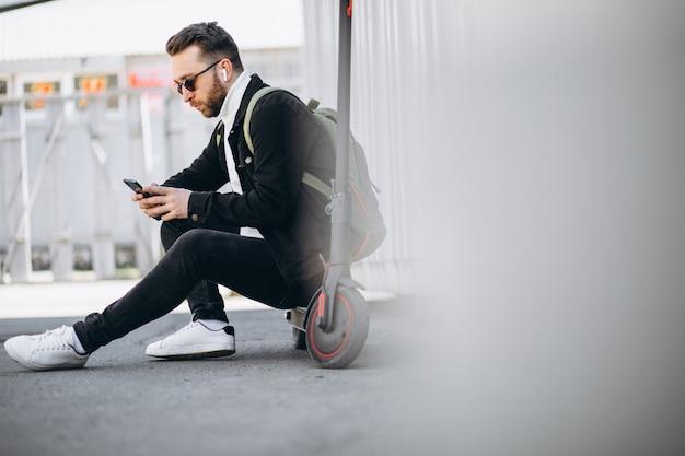 スクーターの電話でのオンラインショッピングでハンサムな男