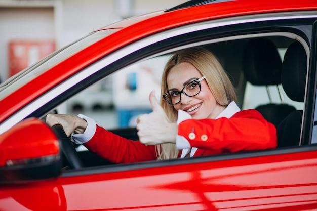 Бизнес женщина сидит в новой машине в автосалоне