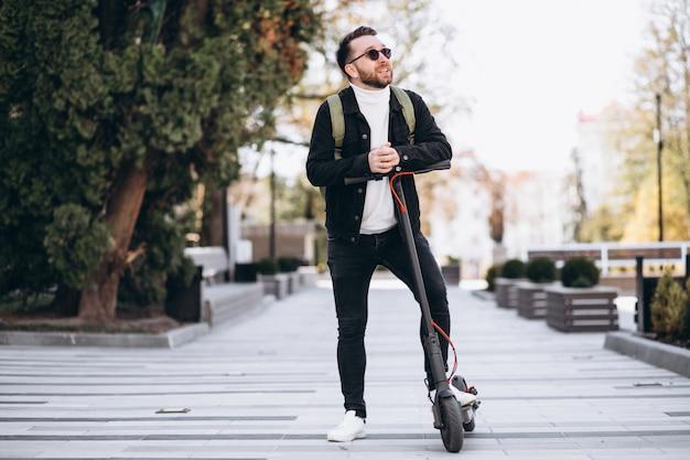 公園でスクーターに乗って若いハンサムな男