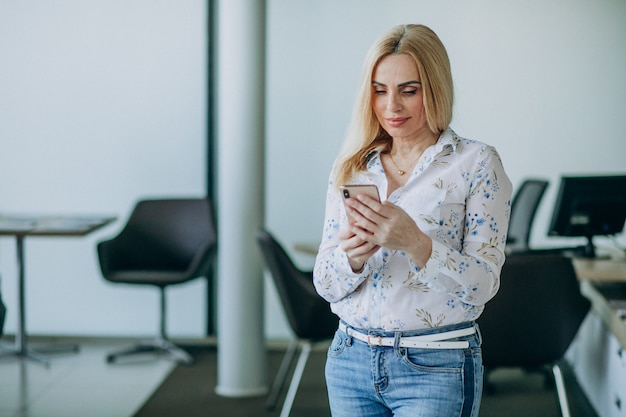 電話を使用してオフィスでのビジネスの女性