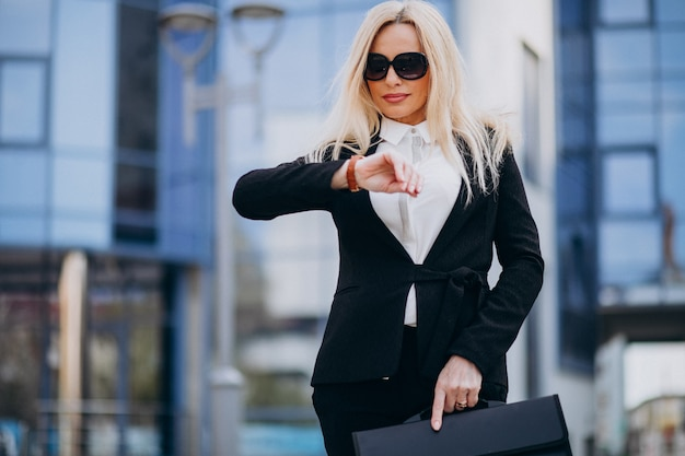 ビジネスセンターでスーツケースを持つ中年のビジネス女性