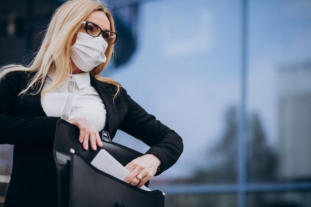 ビジネスセンターの外のマスクを身に着けているビジネス女性