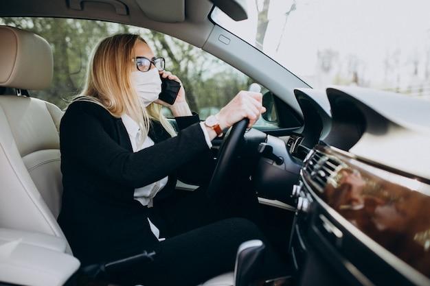 Деловая женщина в защитной маске сидит в машине