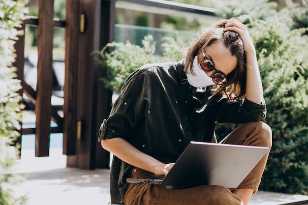 マスクで自宅からコンピューターに取り組んでいる若いビジネス女性
