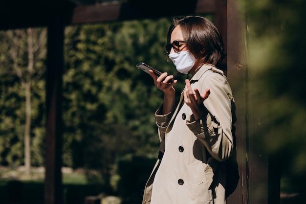 顔の保護マスクを持つ若い女性