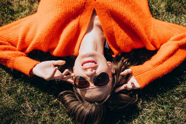 Красивая женщина, лежа на траве в красочный свитер