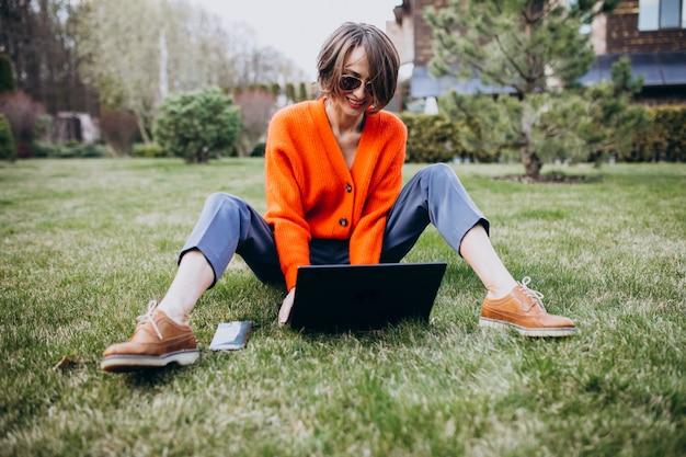 草の上のラップトップを持つ若いビジネス女性