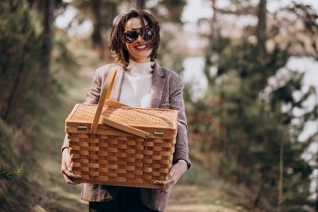 森の中のピクニックボックスを持つ若い女