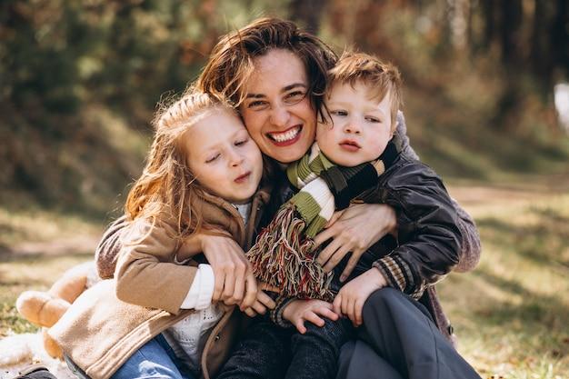 森の中のピクニックを持つ子供を持つ母